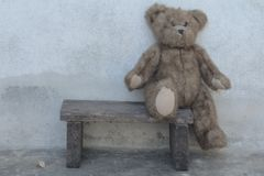 O urso de peluche bonito senta-se para baixo no assento Fotografia de Stock Royalty Free