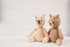 O urso de peluche dos pares com coração vermelho faz crochê a confecção de malhas feito a mão, o amor e o conceito do Valentim fotografia de stock