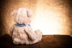 O urso de peluche está sentando-se na tabela de madeira velha Imagens de Stock Royalty Free