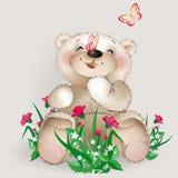 O urso de peluche feliz senta-se em flores de um prado Fotos de Stock Royalty Free