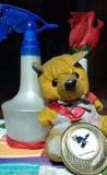 O urso de peluche pequeno que veste uma medalha junto com uma garrafa do pulverizador da rosa e de água dentro atrás imagens de stock royalty free