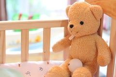 O urso de peluche senta-se na cama das crianças Fotos de Stock