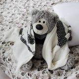 O urso do brinquedo senta-se em uma cama rolada acima em uma manta Foto de Stock Royalty Free