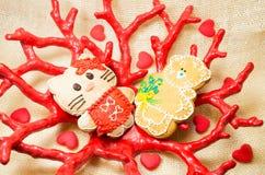 O urso e o gato pequenos doces do pão-de-espécie no coral vermelho dão forma ao vaso Imagens de Stock Royalty Free
