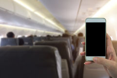 O uso da mulher seu telefone no avião borrou o fundo Imagens de Stock