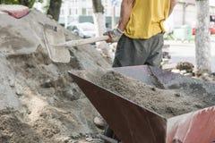 O uso do trabalhador a pá e enche o carrinho de mão com a areia para a construção da estrada do passeio Ferramentas da construção fotos de stock royalty free