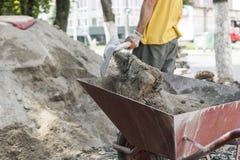 O uso do trabalhador a pá e enche o carrinho de mão com a areia para a construção da estrada do passeio Ferramentas da construção imagem de stock