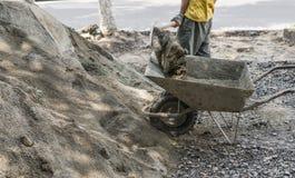O uso do trabalhador a pá e enche o carrinho de mão com a areia para a construção da estrada do passeio Ferramentas da construção imagens de stock royalty free