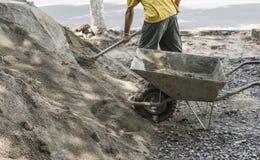O uso do trabalhador a pá e enche o carrinho de mão com a areia para a construção da estrada do passeio Ferramentas da construção foto de stock