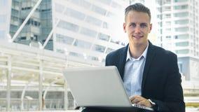 O uso esperto do homem o portátil do computador no público exterior Imagem de Stock