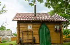 O utensílio e o barco do agregado familiar penduram na parede do bathhouse Imagens de Stock