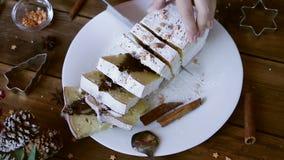 O vídeo da mão da mulher cortou o bolo de chocolate do Natal com decoração do feriado Fundo do xmas do alimento video estoque