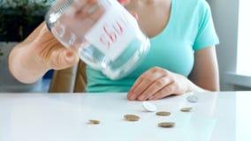 o vídeo 4k da jovem mulher tem poucas moedas no frasco de vidro para economias video estoque