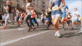 O vídeo unfocused do movimento lento dos marathoners corre na rua no dia ensolarado quente vídeos de arquivo