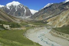 O vale da montanha com picos e rio da neve meanders Imagem de Stock Royalty Free