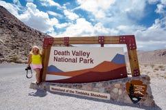 O VALE DA MORTE, CA: Sinal para o parque nacional de Vale da Morte em um dia de verão nublado Poses do fotógrafo da mulher foto de stock
