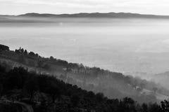 O vale encheu-se pela névoa, com uma estrada e as árvores no primeiro plano Fotos de Stock