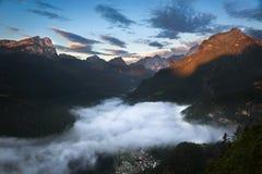 O vale nas dolomites com amanhecer nubla-se, cumes, Itália Imagens de Stock