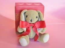 O Valentim encheu o coelho com curva vermelha e a caixa de presente com corações imagem de stock