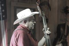 O vaqueiro joga o instrumento baixo Fotografia de Stock Royalty Free