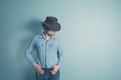 O vaqueiro novo está estando por uma parede azul Fotografia de Stock Royalty Free