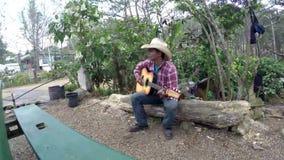 O vaqueiro que ensaia, jogos, sua guitarra senta-se no fazer logon um o dia de verão morno video estoque