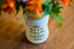 O vaso de flor com ` do texto mantém a calma e continua o ` Imagem de Stock