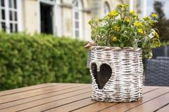 O vaso de flores de vime com teste padrão da coração-forma com flores amarelas está estando na tabela Foto de Stock