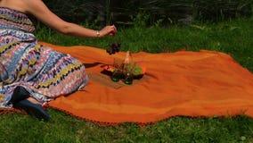 O vaso do fruto do piquenique, vidro da água, mulher come a uva no dia ensolarado Fotos de Stock Royalty Free
