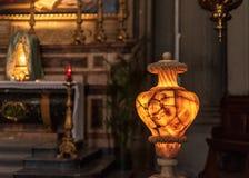 O vaso iluminado antigo do alabastro mostra a cara do Medusa e de quebras numerosas fotografia de stock
