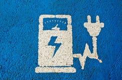 O veículo elétrico que carrega o sinal público da estação no azul pintou o asfalto foto de stock royalty free