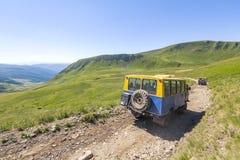 O veículo fora de estrada vai na maneira de estrada do cascalho da montanha Imagens de Stock Royalty Free