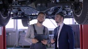 O veículo técnico da condição das inspeçãos do auto mecânico no elevador mecânico com o cliente em homens felizes do serviço do c video estoque