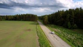 O veículo utilitário do esporte conduz ao longo da opinião aérea da estrada cinzenta vídeos de arquivo