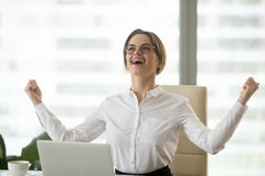 O vencedor seguro excitado da mulher de negócios que comemora a vitória aprecia imagem de stock