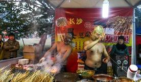 O vendedor ambulante com uma máscara que vende o assado na mostra da lanterna, chengdu, porcelana Imagens de Stock