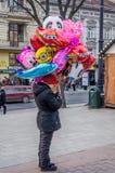 O vendedor da mulher vende balões de ar coloridos com personagens de banda desenhada em Lviv no quadrado perto do teatro da ópera Foto de Stock Royalty Free