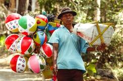 O vendedor de balões dos brinquedos das crianças vende de porta em porta sua mercadoria na vila de Ngebel imagem de stock royalty free