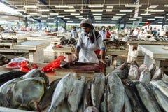 O vendedor de peixe cortou peixes para a venda em semi-exterior, mercado do marisco do ar livre perto da estação de metro de Deir Imagem de Stock Royalty Free