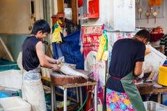 O vendedor de peixe limpa peixes frescos Imagens de Stock Royalty Free