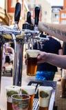 O vendedor derrama peritamente a cerveja fresca no vidro fotos de stock royalty free