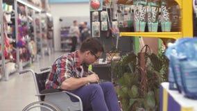 O vendedor do homem com uma inabilidade em uma cadeira de rodas põe os bens sobre as prateleiras na loja video estoque
