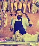 O vendedor do homem que prepara a carne para vender nos butcher's compra imagem de stock