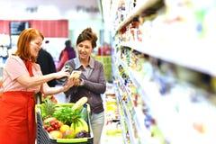 O vendedor do supermercado recomenda um cliente - vendas dos alimentos frescos imagem de stock