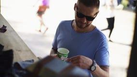 O vendedor do suporte dá o folheto masculino da mercadoria do cliente vídeos de arquivo