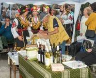 O vendedor do vinho local nos jogos de Nestinar na vila de Bulgari, Bulgária Imagens de Stock