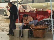O vendedor e o comprador no mercado rural Guilin Foto de Stock