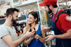 O vendedor está mostrando pares de alicates novos dos clientes na loja das ferramentas elétricas Imagem de Stock