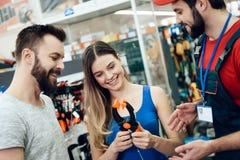 O vendedor está mostrando pares de alicates novos dos clientes na loja das ferramentas elétricas Imagens de Stock Royalty Free