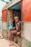 O vendedor indiano não identificado senta-se na janela de sua loja da rua colorida em cores da bandeira nacional em Jodhpur, Índi Fotos de Stock Royalty Free